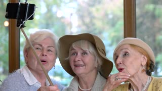 Three senior ladies taking selfie. Women smiling for a photo. Save friendship after many years.