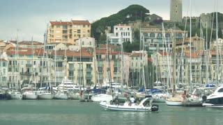 Town buildings and yachts. People in small motorboat. Spend vacation in Cannes.