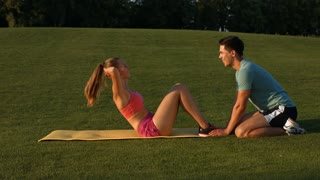 Trainer is engaged in sports with a girl on the green grass. Girl shakes her pres on the nature. Outdoor sports.