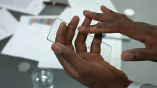 Transparent phone in male hands. Guy holding blank smartphone.