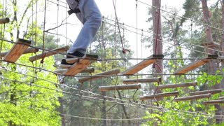 Treetop adventure park at daytime. Ropes and wooden planks. Keep balance and be careful.