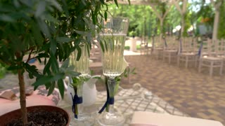 Two glasses of champagne. Chairs with bouquets and ribbons. Seats for wedding guests.