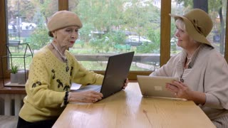 Two old women and laptop. Elderly ladies with tablet. Compare download speed.