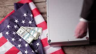 US flag, suitcase and dollars. Hand puts money into case. Refusal is unacceptable. Time to find new allies.