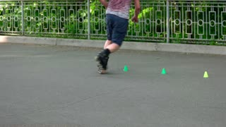 09. 05. 2018, Ukraine, Kiev. Roller skater doing crossover tricks outdoors. Training agility markers. Unrecognizable man.