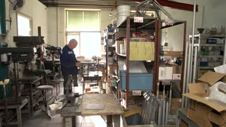 13. 12. 2016 - Kiev, Ukraine. Man in the workshop. Worker and part of engine. From details to prototypes.