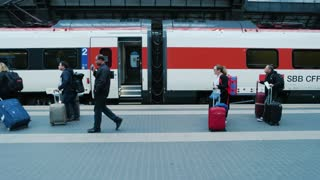 18. 06. 2016 - Milan, Italy. Train station, people with luggage. Passenger train side view.