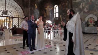 19. 07. 2015 Kiev, Ukraine, Kiev-Pechersk Lavra. Wedding ceremony in a huge church. Paintings on the walls of the cathedral. Bride and groom in the church. The interior of the beautiful cathedral.