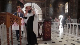 19. 07. 2015 Kiev, Ukraine, Kiev-Pechersk Lavra. Wedding ceremony in a large beautiful church. Priest conducts the wedding ceremony. Rich interior of the ancient cathedral.