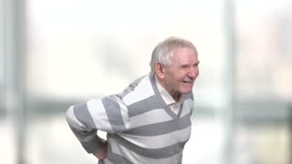 A senior man suffers from pain. Elderly man having pain in back, blurred background.