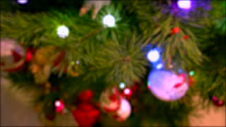 Abstract blurred New Year background. Defocused New Year tree with lights and decorations close up. Happy holidays background.