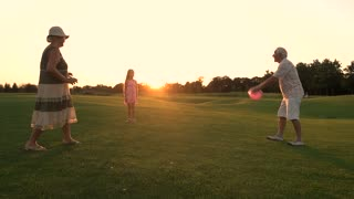 Active family rest on nature with ball. Slow motion senior people and their granddaughter having fun with ball in countryside, sunset sky. Active elderly people.