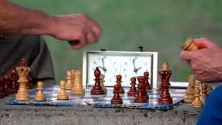 Active retired people, two old friends playing chess at park. Old homemade chess close up.