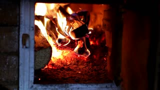 Adding firewood to the burning fireplace. A cozy fireplace in the house. Brightly burning flame.