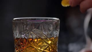 Adding fruit slice to the cocktail. Close up alcohol drink, slow motion.