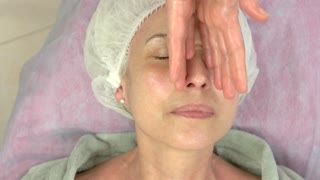 Adult woman having lymphatic massage. Hands massaging face and neck.
