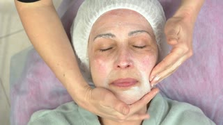 Adult woman, lymphatic face massage. Hands applying skin cream.