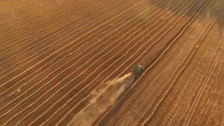 Aerial view of moving harvester. Trail of dust behind machine. Big farm has rich crops. Provide food for entire country.
