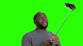 African american man using monopod. Cheerful dark-skinned man taking a picture with selfie stick on Alpha Channel background.