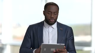African black man with tablet speaking at business seminar. Portrait of charismatic black man in suit holding tablet and talking at business conference in bright office.