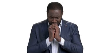 African businessman in desperate praying to god. Crying black businessman with clasped hands near chest. Deep depression and stress because of death of family member.