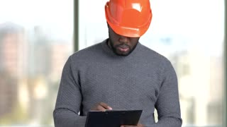 Afro american architect writing down notes on clipboard. Black worker with clipboard, pen and orange helmet indoor, window background.