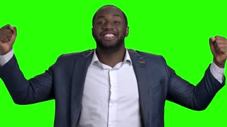 Afro american businessman celebrating victory. Slow motion excited afro american entrepreneur expresses satisfaction and triumph on green screen background.