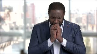Afro-american businessman is crying on blurred background. Stressed dark-skinned man in business suit is crying. Black entrepreneur is praying.