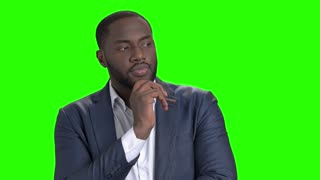 Afro-american businessman is thinking on green screen. Thoughtful dark-skinned businessman with hand on chin on Alpha Channel background.