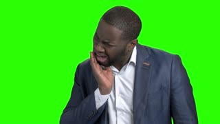Afro american businessman suffering from tooth ache. Dark-skinned manager touching his cheek because of strong tooth pain on chroma key background. Stomatology and dentistry concept.