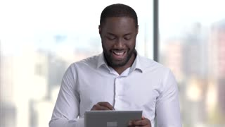 Afro-american businessman using pc tablet. Black businessman with digital tablet on blurred background.