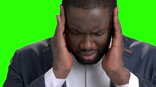 Afro american businessman with strong headache. Young dark-skinned man in formal wear suffering from terrible headache on green screen close up.