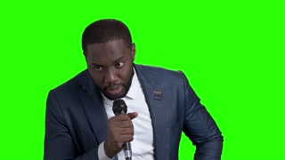 Afro-american entertainer talking on green screen. Dark-skinned man in elegant suit talking into microphone on chroma key background.