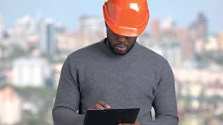 Afro-american foreman on blurred background. African-american architect in hard hat writing on clipboard. People, construction, maintenance.