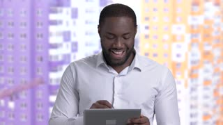Afro-American guy in white shirt using pc tablet. Successful african-american architect working pc tablet on construction background.