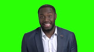 Afro american man making grimace on green screen. Dark skinned businessman making funny face on Alpha Channel background.