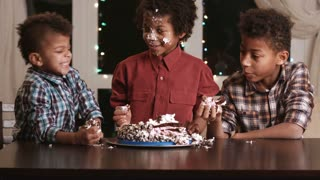 Afro boy's face smashing cake. Kid smashes cake with face. Have a small bite. Here's a true gourmet.