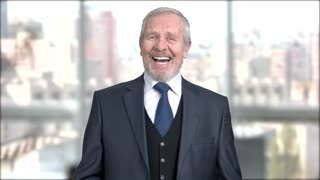 Aged man in formal wear is laughing. Caucasian older corparate is laughing on window city background. Funny senior executive.