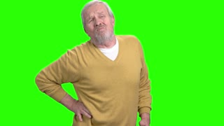 Aged man suffering from back pain. Elderly man having pain in back, green screen. Spinal ache concept.