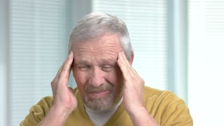 Aged man with severe headache close up. Handsome bearded senior man pressing his fingers to his temples, blurred background. Symptoms of high blood pressure.