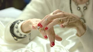 Aged woman hands with luxury rings. Well-groomed hands of senior woman with perfect red manicure wearing expensive jewelry. Elegance and perfection concept.