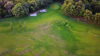 Amazing scenery of park nature, aerial view. Spring scene of green forest with meadow, aerial drone view. Golf courses from the air.