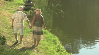 Amusing couple of seniors near water. Elderly man and woman holding hands and hugging each other on summer nature background. Romantic walk together in sunny day.