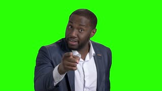 Angry businessman on chroma key background. Displeased afro-american entrepreneur arguing on Alpha Channel background and gesturing with finger.