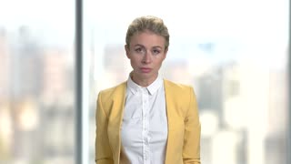 Angry businesswoman talking on bright office background. Portrait of serious strict aggressive nervous stressed office woman blaming and accusing you.