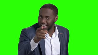 Annoyed afro-american businessman on green screen. Arrogant african american man in business suit accusing and humiliating somebody on chroma key background.