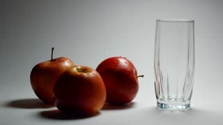 Apple fresh juice with red apples. Apple juice is poured into a glass. Apple drink. Still life of apples on a white background.