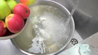 Apples falling in water, top view. Ripe fresh apples falling in a bowl of water, metal bowl in a sink.