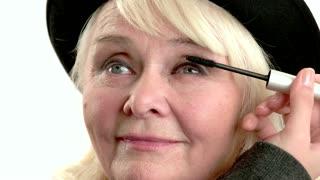 Applying makeup on old woman. Hand with eyelash brush.