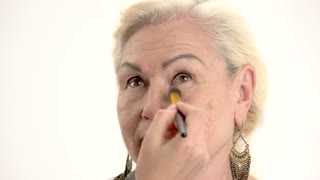 Applying makeup on senior lady. Female hand with cosmetic brush.